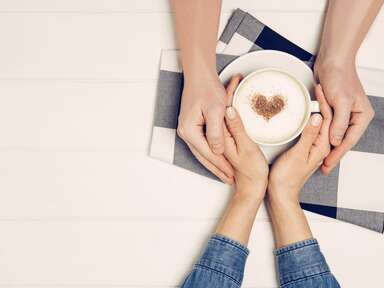 Couple holding hands over a cup of coffee