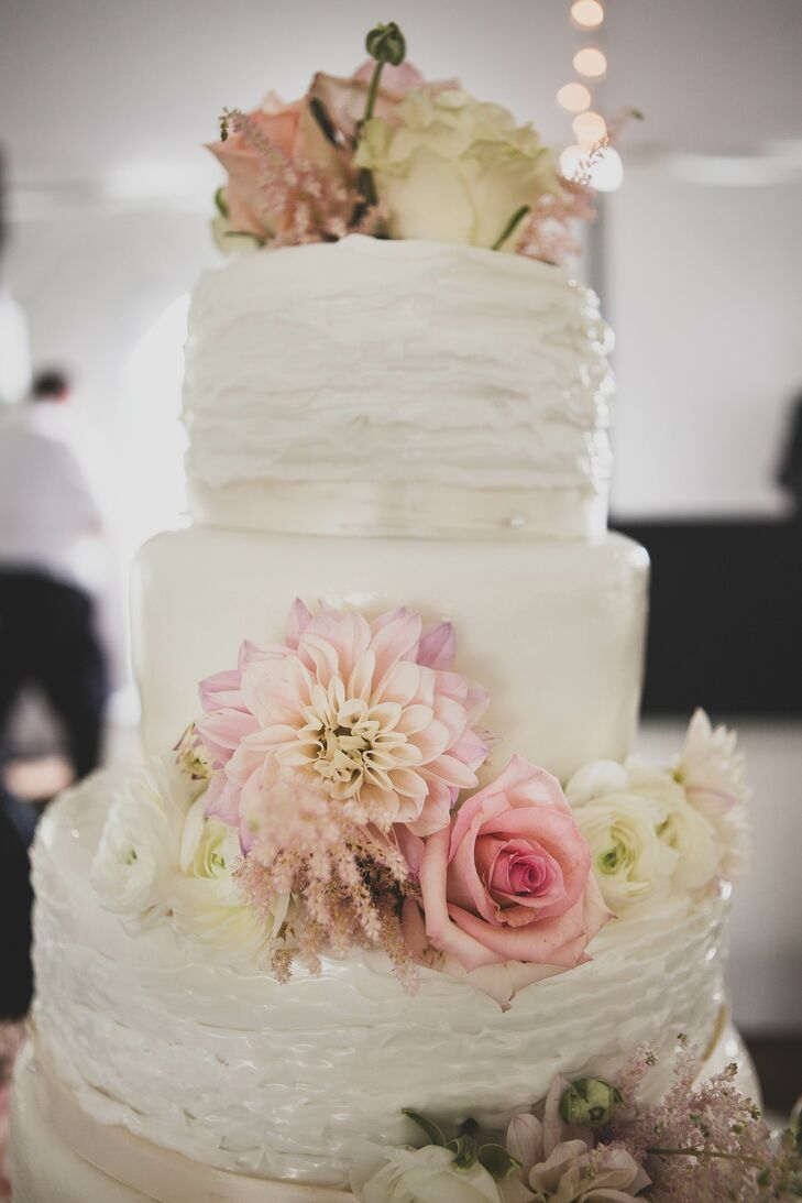 """""""Our wedding cake was such a hit, we didn't even get a piece,"""" the bride says. The six-tier cake looked sweet and romantic with ruffled fondant and fresh pink flowers surrounding alternating layers."""