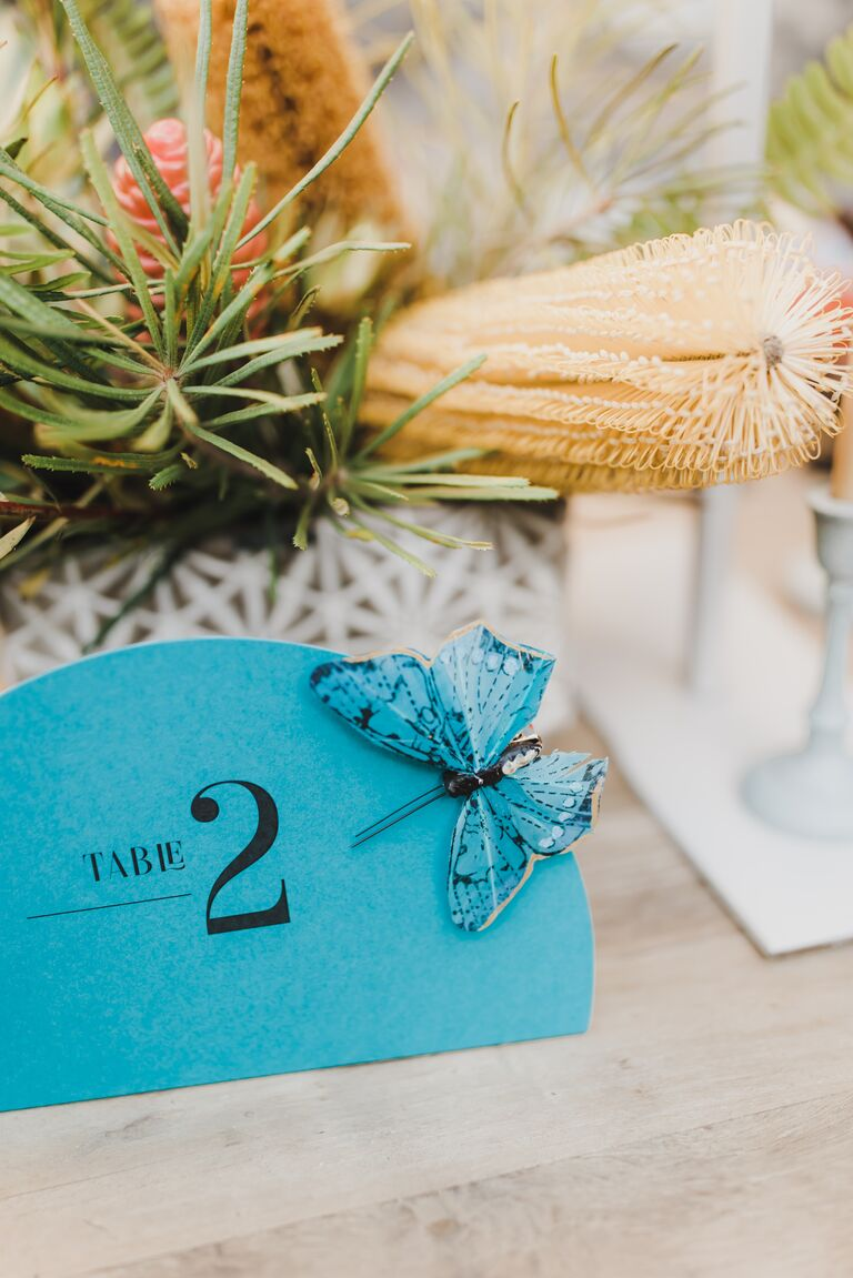 closeup of wedding table number blue card with fake butterfly
