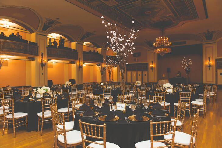 """Gold chiavari chairs and dinnerware popped against all-black linens within the airy ballroom space. """"Our color scheme fit our venue perfectly,"""" Laurie says. """"We loved the old charm of the venue and gold and black made everything seem so elegant."""""""