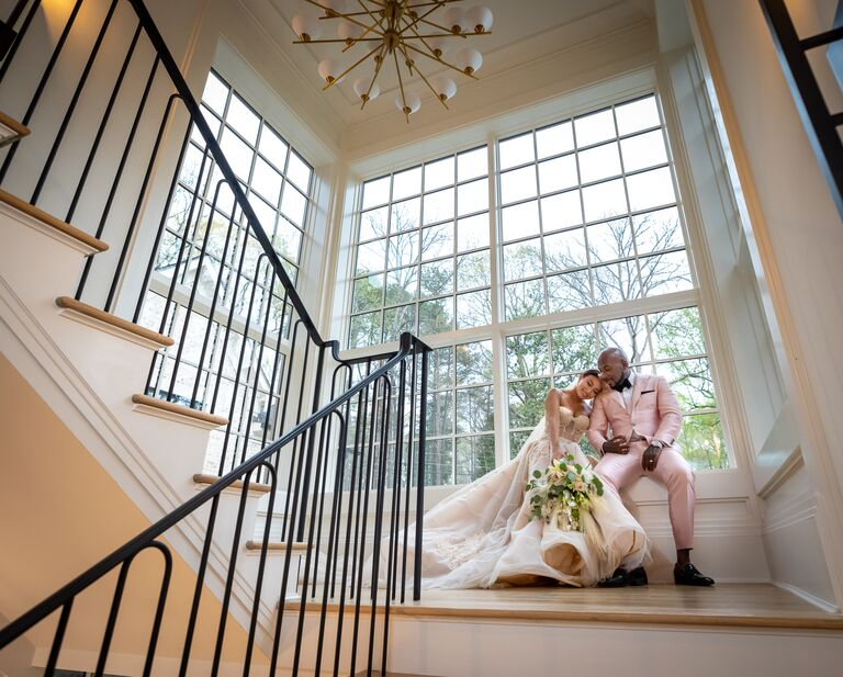 jeannie and jeezy in front of stairwell and open windows on wedding day