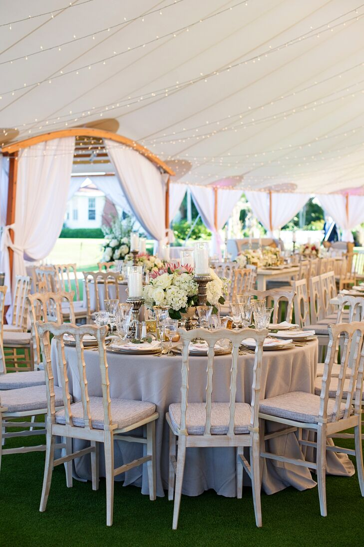While gilded accents, pillar candles and bold bouquets of hydrangeas, roses and proteas arranged in footed bowls gave the reception a sense of elegance and refined flair, antiqued wooden chairs and a Sperry tent infused the decor with a subtle rustic note.