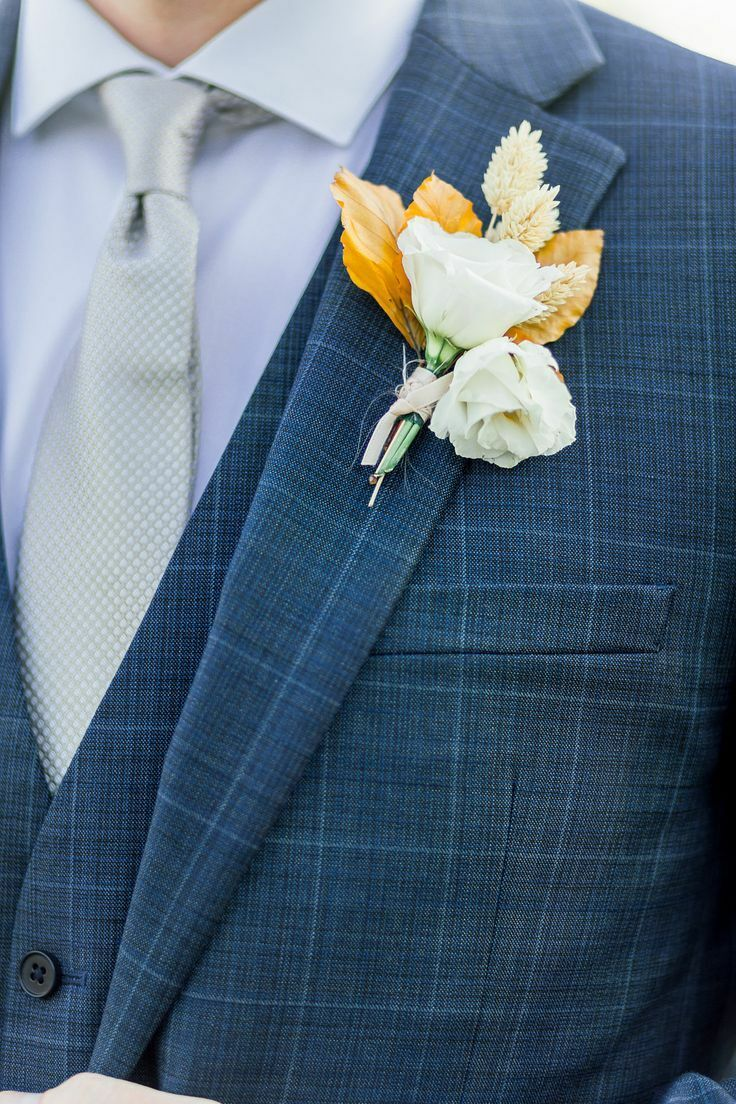 Boutonniere with white flower and dried leaves
