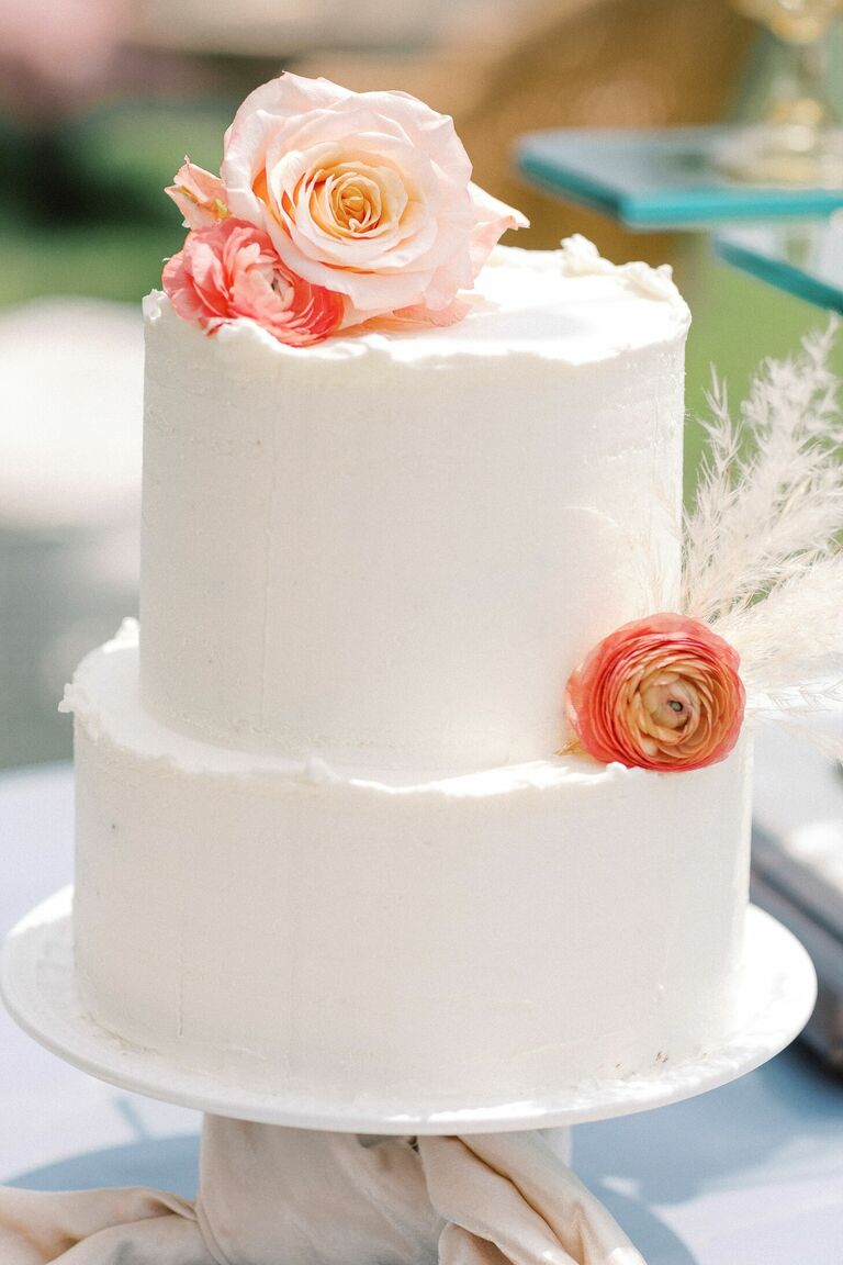 White two-tier wedding cake with fresh flowers