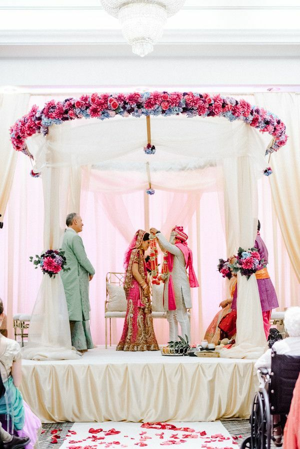 Couple underneath pink-and-white mandap in ballroom