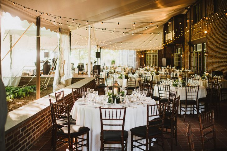 The reception was held on a tented brick porch at Greenville Country Club. Bistro lights were strung from the ceiling. Tables were covered in white tablecloths and featured lantern centerpieces.