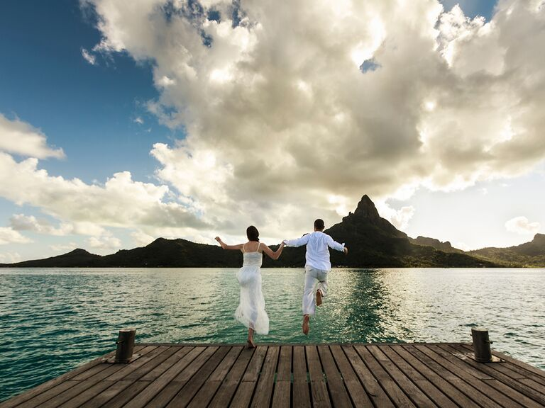 Newlywed couple jumping from a wood pier into sea of Bora Bora, French Polynesia