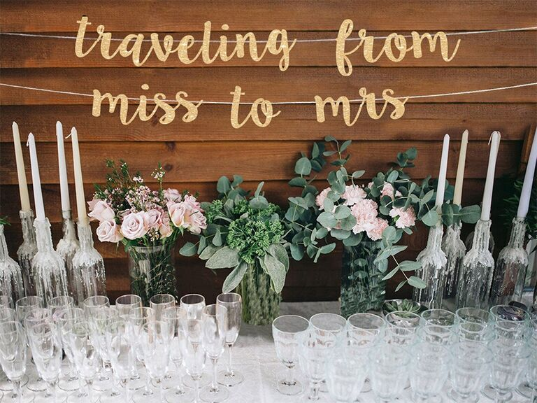 'traveling from miss to mrs' in sparkly gold script banner
