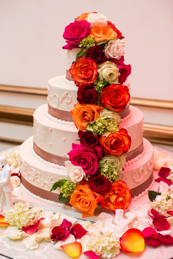 """Their cake was Michelle's favorite part. """"I thought it was too pretty to cut,"""" she says. They made sure the four-tier confection was dripping with flowers to match the centerpieces. Cascading orange, red, pink and white roses touched every tier, and the base was surrounded with petals. If that wasn't enough, a neutral ribbon and a bold fondant design circled every tier."""