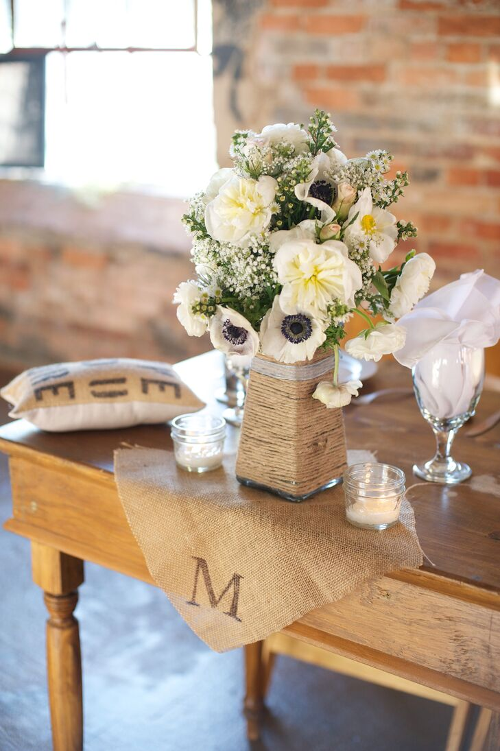 Tara arranged all of the floral arrangements for the ceremony herself, using ivory anemones, peonies and baby's breath. She placed each rustic arrangement in a vase wrapped in twine.