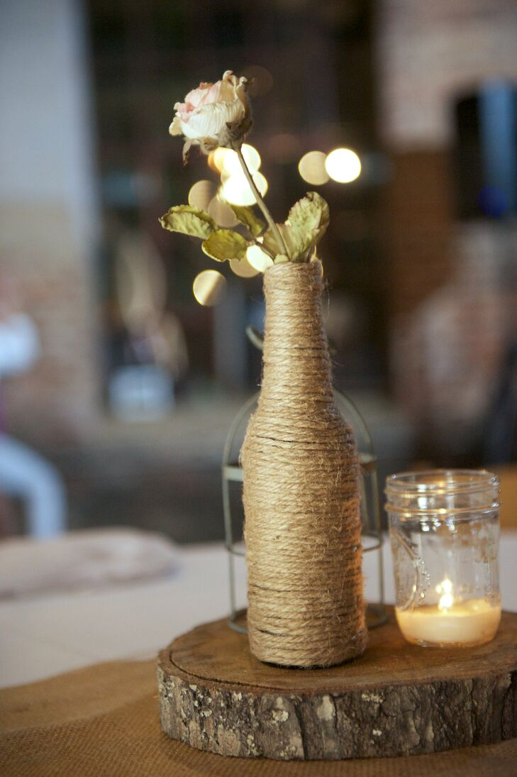 In addition to the lush ivory floral arrangements, the reception tables were also decorated with simple bunches of ivory spray roses placed in homemade twine-wrapped vases.
