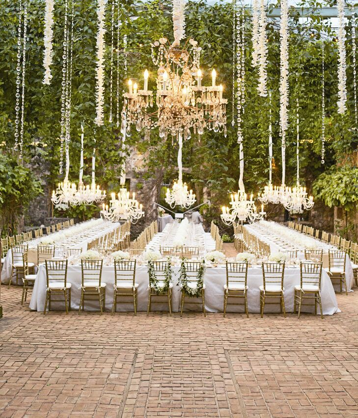 Lush hanging vines, orchids and chandeliers mixed with white linens and gold chiavari chairs made for a sophisticated reception setting.