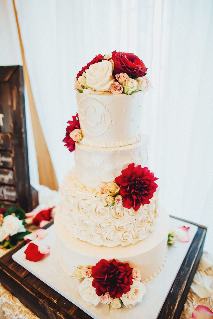 Andrew made the DIY square cake stand for an impressive four-tier wedding cake. It had four flavor combinations with ivory buttercream decorating each tier—smooth, rosettes, textured and Swiss dots with the newlyweds' custom monogram. Ivory, blush and maroon flowers added a romantic touch.