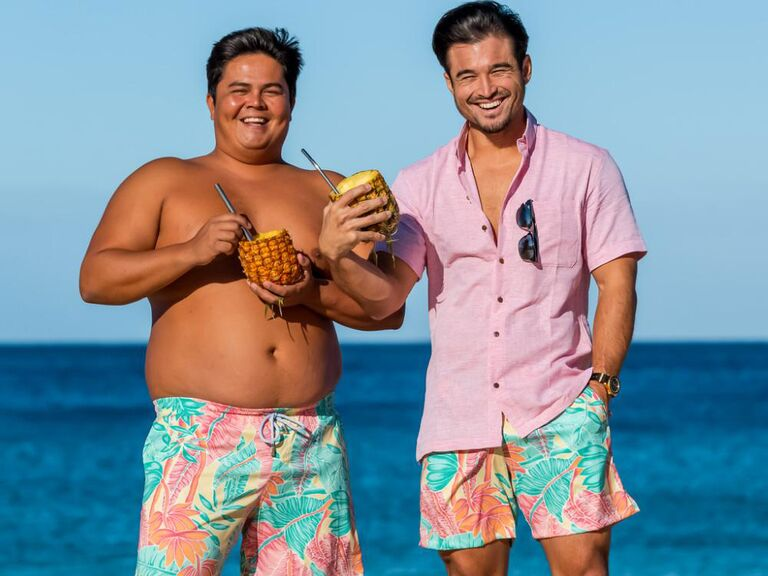 Couple wearing matching monstera print swim trunks and holding cocktails