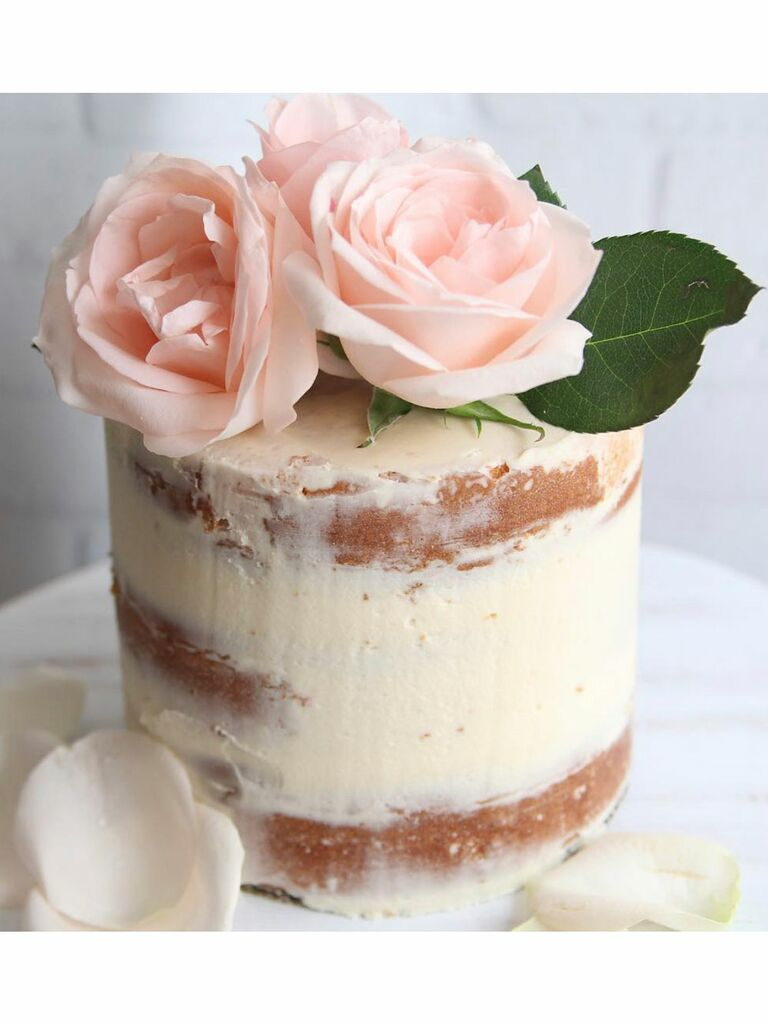 Semi-naked bridal shower cake with pink flowers on top