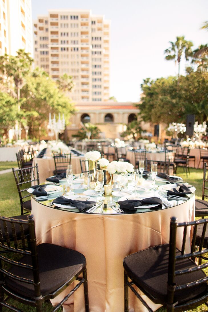 Each glass topped round table was met with gold linens, a white floral centerpiece with rose or hydrangeas, gold accents and an Art Deco style table number to match their Great Gatsby inspiration.