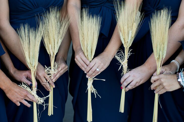Instead of traditional floral bouquets, the bridesmaids carried thin, rustic stalks of wheat for a chic and unconventional accent against their navy dresses.