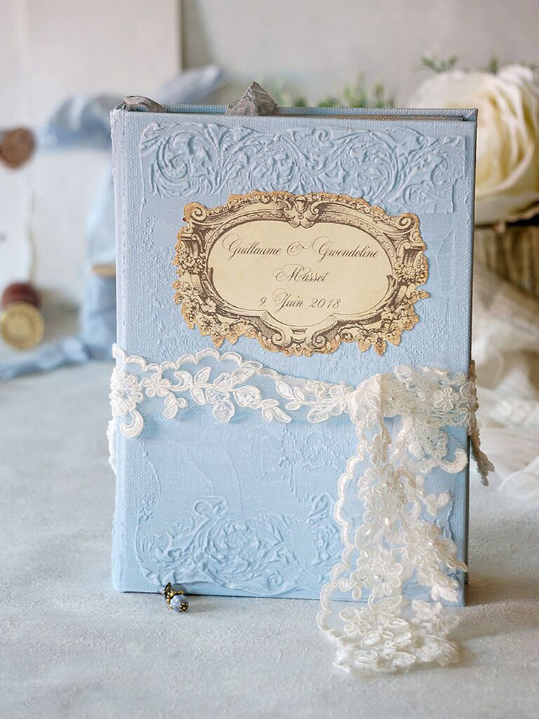 Embossed, imprinted blue guest book with intricate gold label and white floral lace ribbon