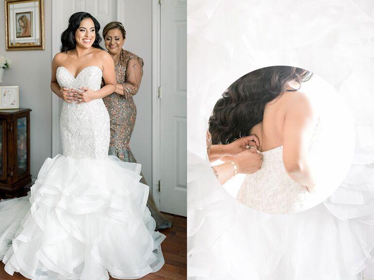 bride putting on wedding dress with mom