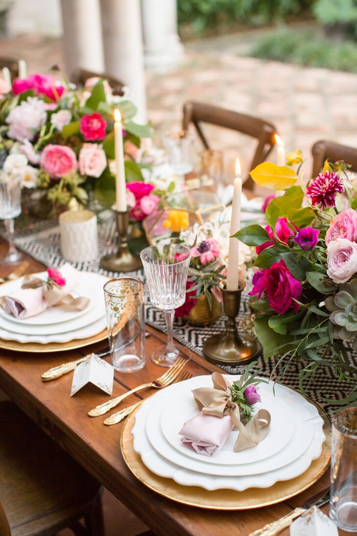 Tables were embellished with blue and white geometric table runners, pretty pink flower arrangements and gold decor.