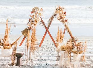 For their beach wedding in Ocean City, New Jersey, Lindsey and John expertly blended a boho-chic aesthetic with a sleek-and-moody color palette. The e