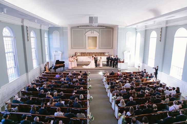 """Christine and Keith had their ceremony at the Prairie Baptist Church in Prairie Village, Kansas. """"It has the most amazing windows throughout the sanctuary,"""" Christine says. """"Right before the wedding ceremony began, to the sound of 'Ode to Joy' on the harp, the windows simultaneously opened to allow a flood of glorious light into the room."""""""