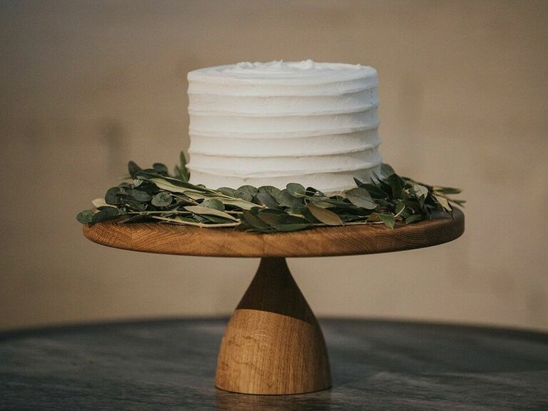 Single-tier rustic cutting cake with white icing and eucalyptus leaves