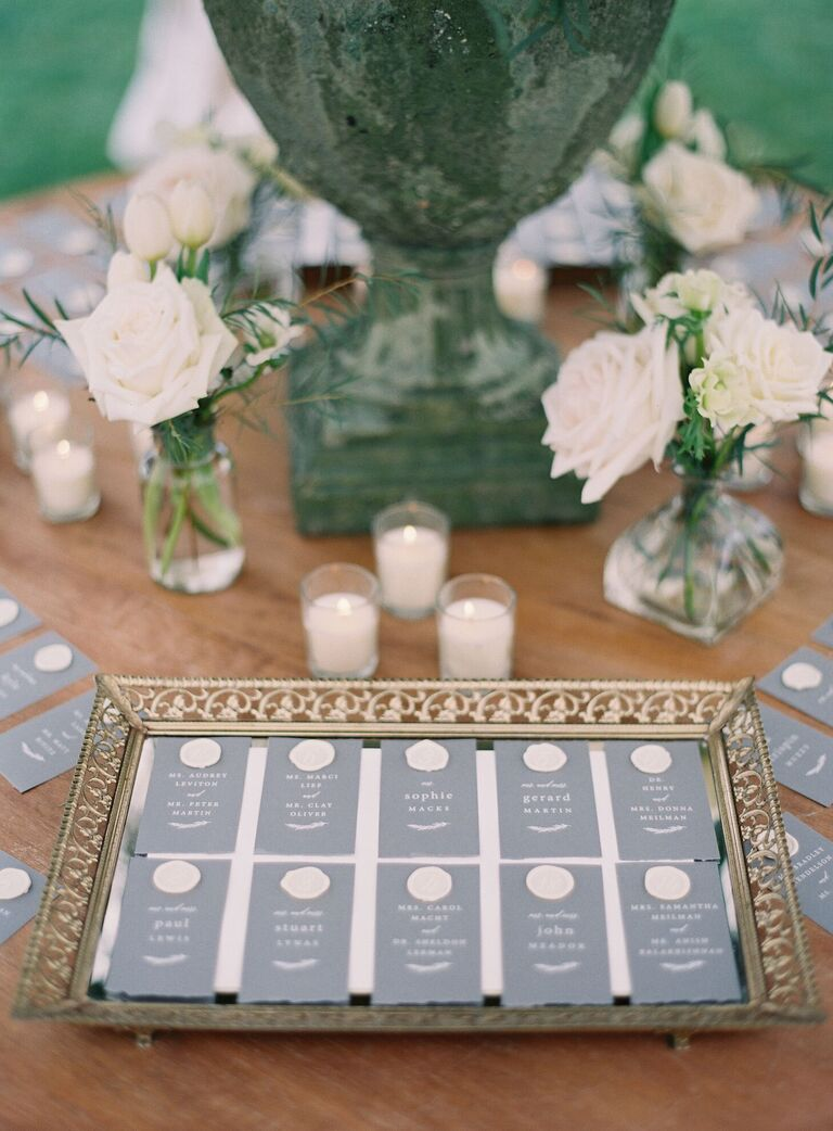 Gray escort cards with white wax seal on vintage gold mirrored tray