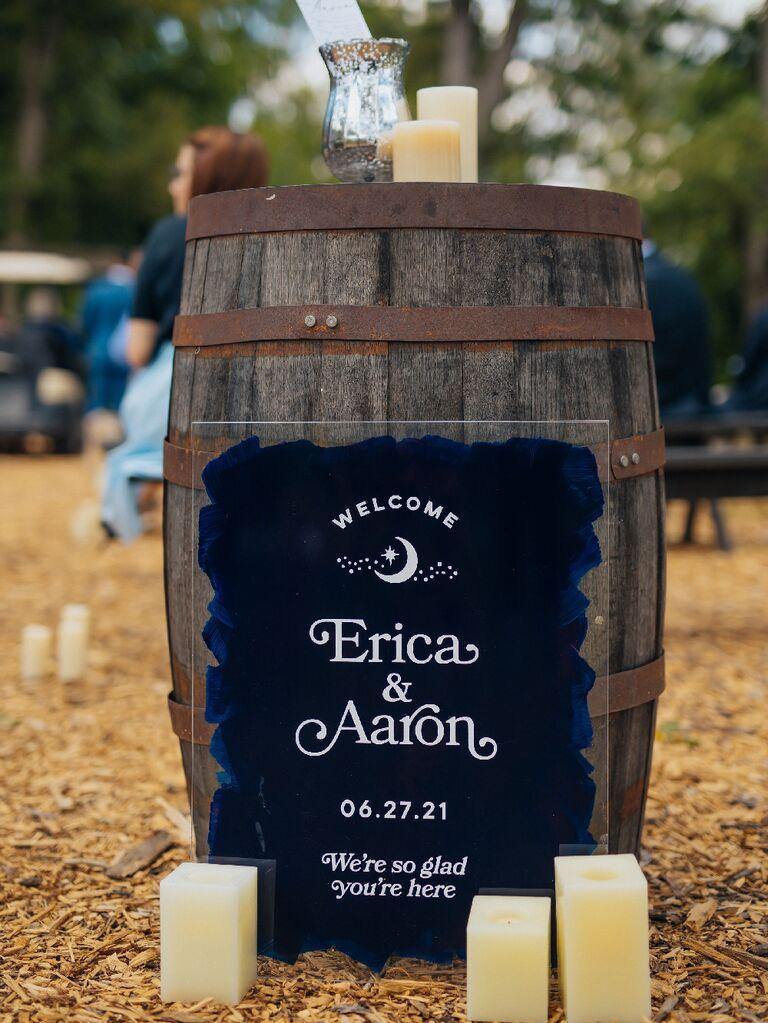 Dark blue celestial wedding welcome sign against barrel at outdoor barn wedding