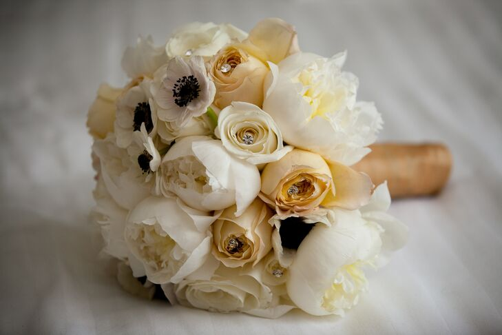 Marielle's bouquet was filled with ivory peonies, garden roses, ranunculuses and anemones, as well as nude-colored roses for a romantic, vintage-inspired feel. Crystal accents added a subtle touch of glitz to the bouquet.