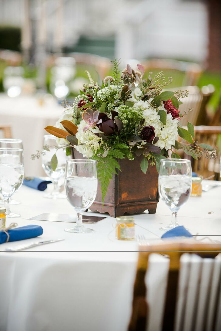 Weathered wood boxes held the centerpieces, which were filled with hydrangeas, succulents, proteas, ferns and veronica.