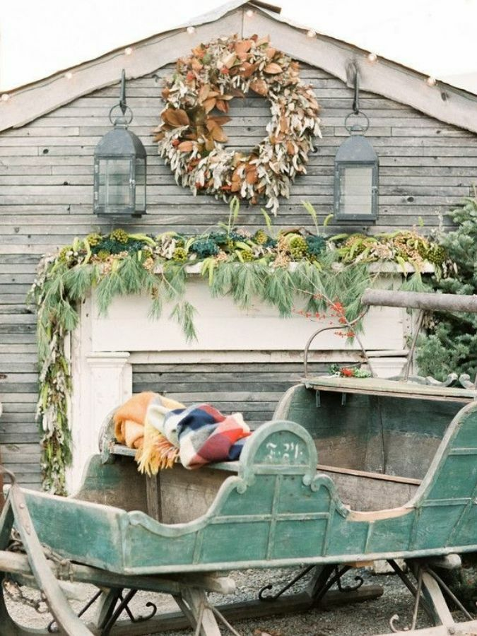 Green sleigh outside rustic barn