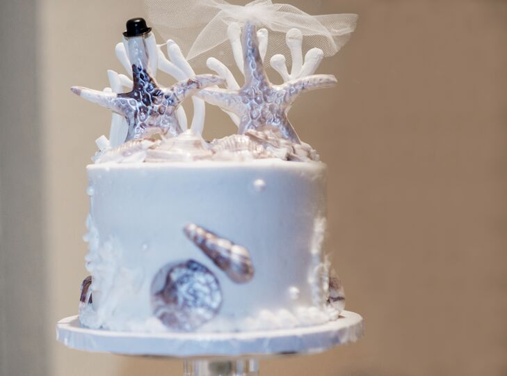 To complement their beach theme, the couple served a single tier cake topped with silver starfish as well as a  chocolate and peanut butter surfboard groom's cake.