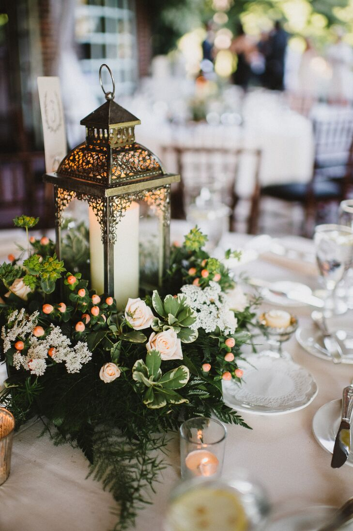 Reception centerpieces featured vintage pewter lanterns surrounded by a ring of greens and peonies with peach berries and votive candles.