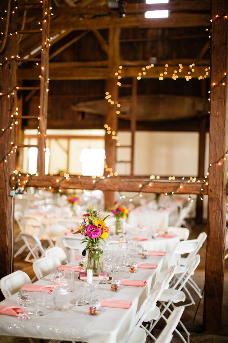 """Kristie and Ryan filled the barn with white round and long reception tables and matching white chairs. Each one had a bright wildflower, daisy and sunflower centerpiece as well as coral napkins and colorful wedding favors. Every favor even alluded to the couple's relationship. """"We decided on jelly beans in the jars because Jelly Bean is a nickname I call Ryan,"""" Kristie says."""