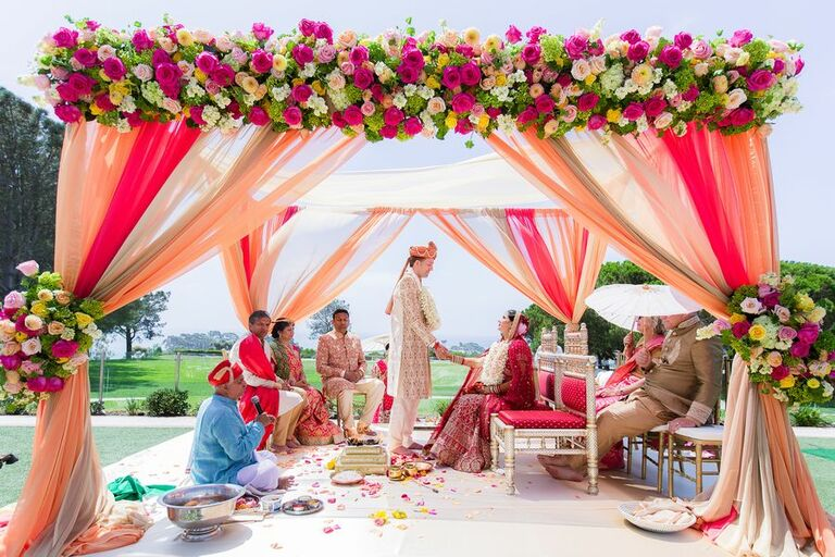Bright pink mandap with draping and floral accents