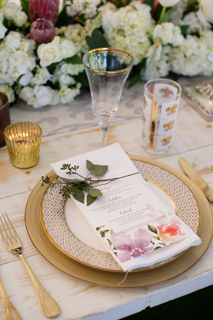 The menu cards doubled as the place cards, with the names of each guest hand calligraphed in playful pink ink. Bearing bright watercolor flowers, they added a pop of color to the stately patterned plates, gold chargers and cutlery.