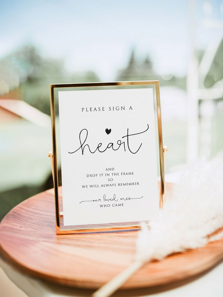 'Please sign for a heart' in minimalist type in gold frame