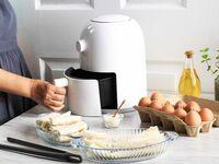 Woman using air fryer in kitchen
