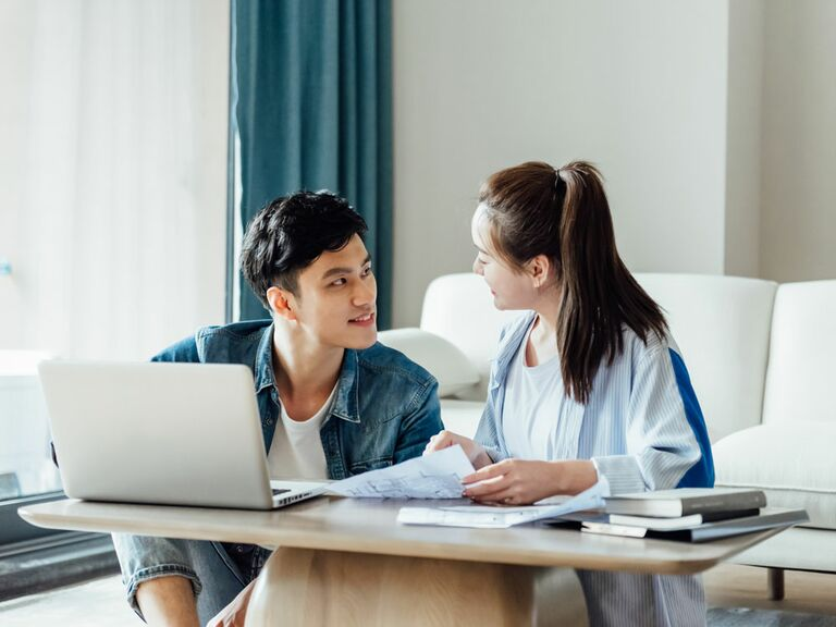 Young couple wedding planning on laptop at home