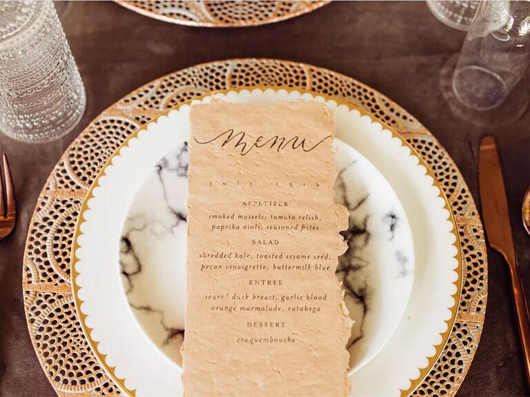 Distressed menu card on marble plate iwth gold edge