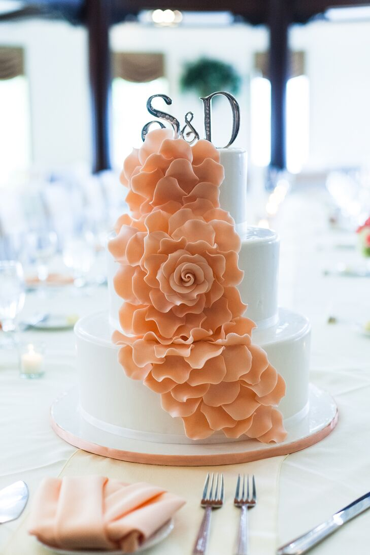 Pink-frosted flowers cascaded down the side of the three-tier white wedding cake.