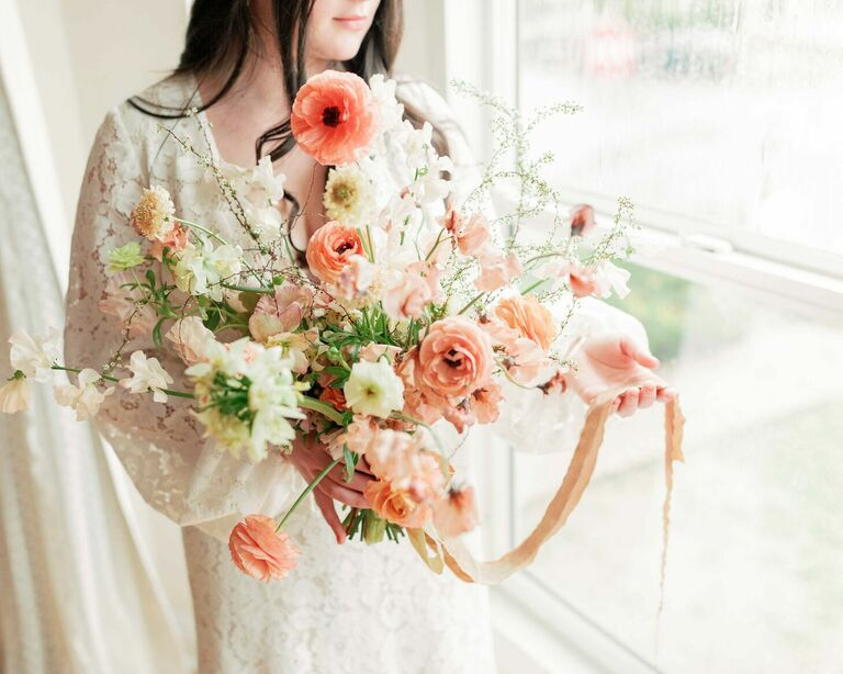 Bride holding whimsical pink poppy wedding bouquet
