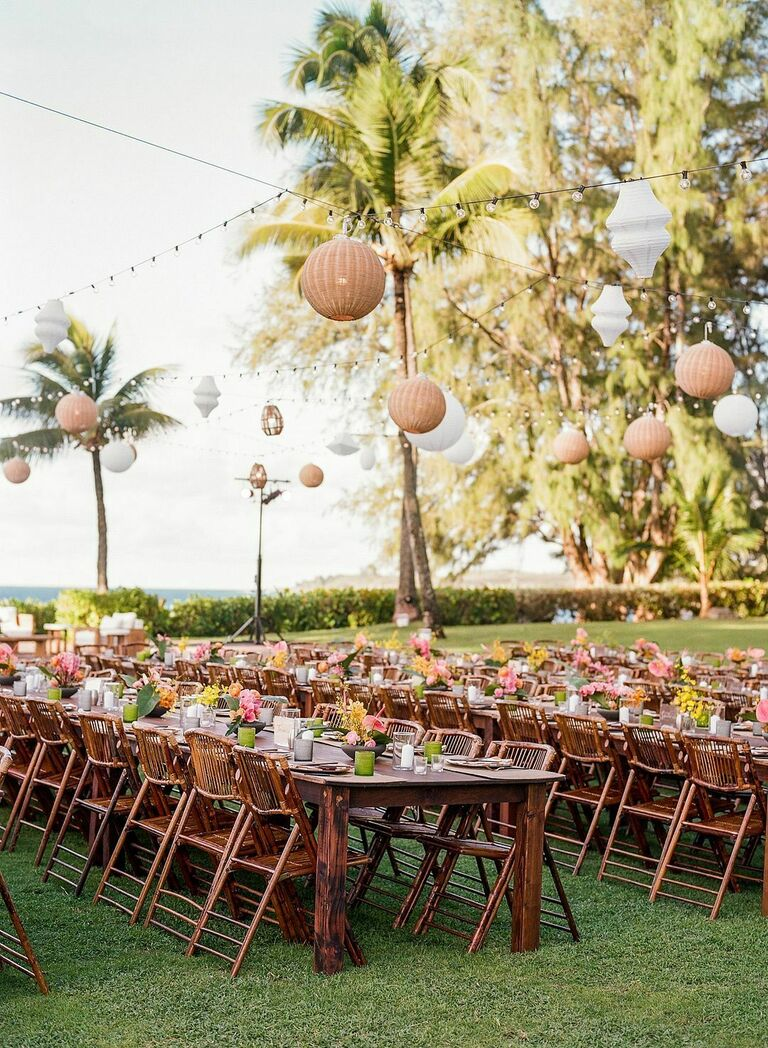 Outdoor wedding reception with farm tables, folding bamboo chairs and woven chandeliers