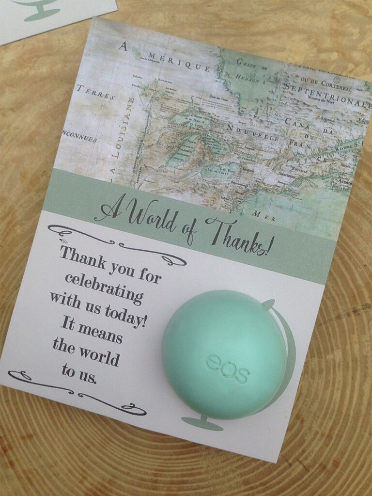 Top half in map design above 'A World of Thanks!' in loopy black script on light green stripe with EOS lip balm positioned as globe on bottom