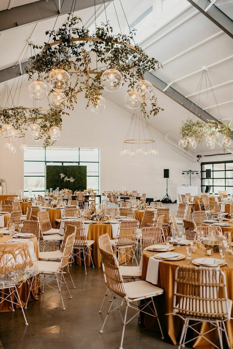 Boho wedding reception with greenery-covered chandeliers and leather chairs