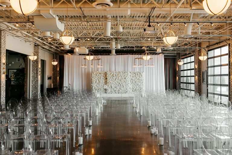 Wedding ceremony in loft with acrylic ghost chairs and white flower wall backdrop