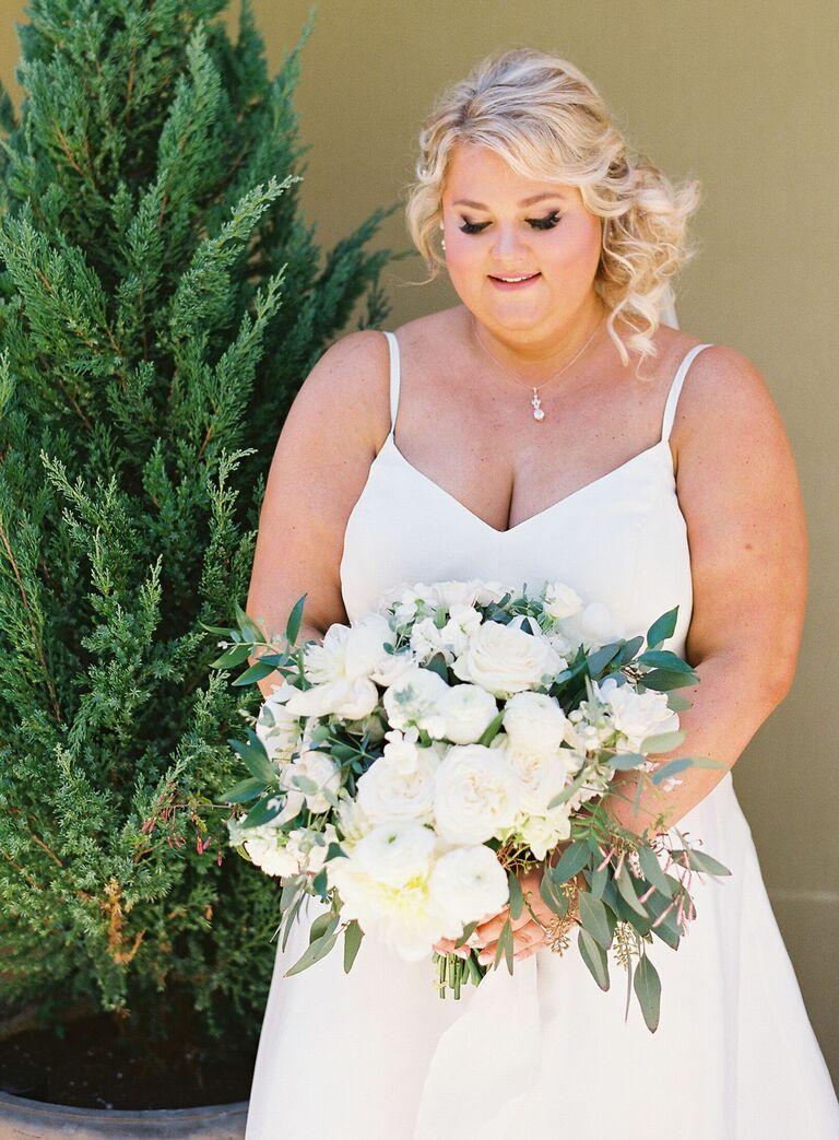Bride holding white bouquet with eucalyptus