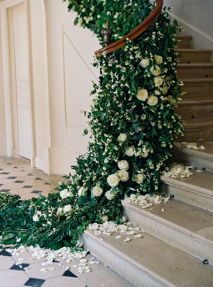 Planner Lindsay Moynagh of House of Hannah and Liv's mother transformed Chateau de Courtomer into a romantic bohemian dream, adorning the stairs with a lavish garland of lilies of the valley, garden roses and greenery, styled alongside loosely scattered white rose petals.
