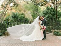 Groom with bride on wedding day wearing cascading cathedral-length veil